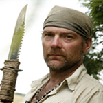Les Stroud holding spear